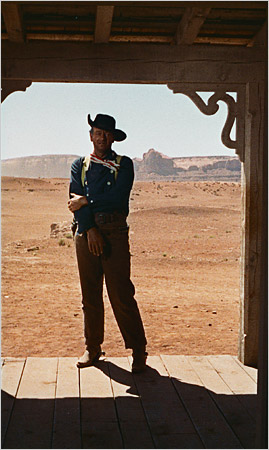 "John Wayne standing in a doorway shot from John Ford's ""The Searchers"""