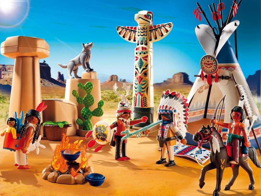 An image of a Playmobil playset that includes a tipi, a totem pole, horses, a coyote, and people dressed in a mishmash of tribal styles in a desert setting.